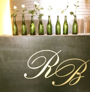Detalle de decoración con botellas y flores en Rexach Baqués