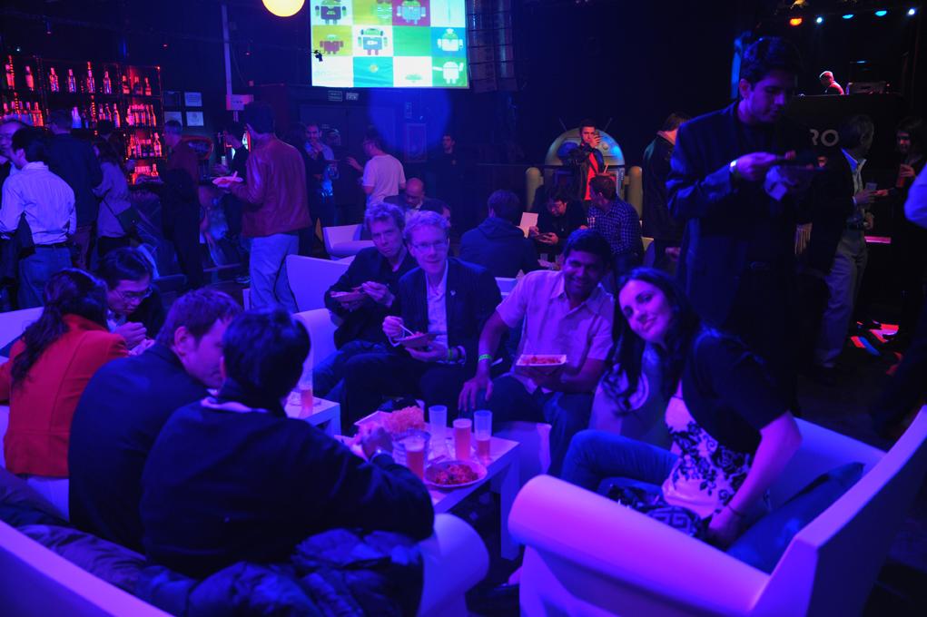 Grupo de personas sentadas en sofá disfrutando la Paella