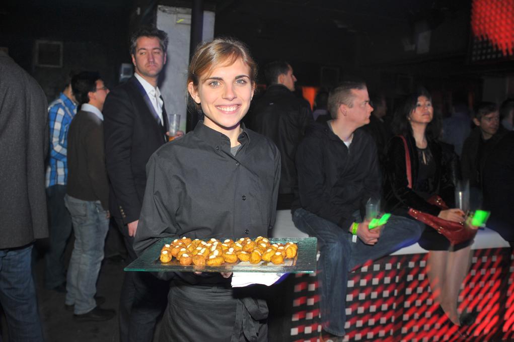 Una camarera sostiene una bandeja con patatas bravas